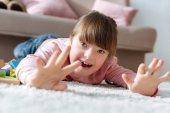 Boldog gyermek feküdt a padlón hangulatos szobában down-szindróma