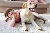 Boldog gyermek down-szindrómás feküdt a padlón a Labrador Vizsla