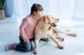 Dítě s Downovým syndromem a Labradorský retrívr dívá stranou v jednom směru
