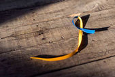 Blue and yellow ribbon on wooden background for Down Syndrome Day background