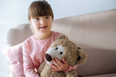 Smiling child with down syndrome sitting on sofa and holding teddy bear