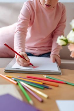 Close-up view of kid with down syndrome drawing with colorful pencils