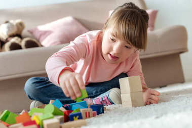 Kid with down syndrome playing with toy cubes