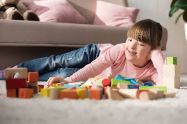 Kid with down syndrome lying on floor and looking at toy cubes