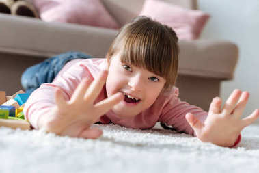 Happy child with down syndrome lying on floor in cozy room