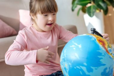 Child with down syndrome looking at globe