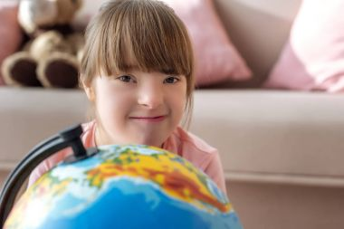 Kid with down syndrome looking at camera over globe