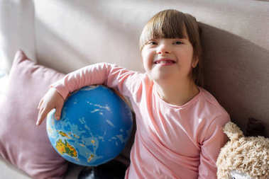 Smiling child with down syndrome holding globe