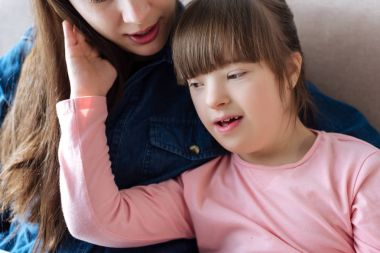 Mother tenderly hugging daughter with down syndrome