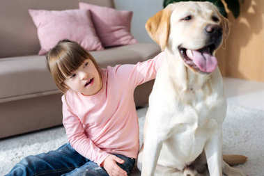 Child with down syndrome stroking Labrador retriever