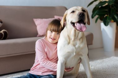 Kid with down syndrome embracing Labrador retriever