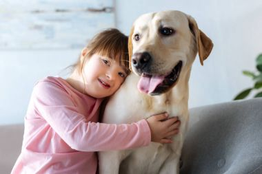 Child with down syndrome embracing Labrador retriever and looking at camera