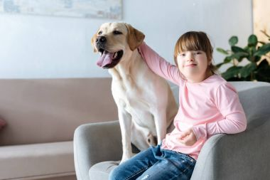 Kid with down syndrome stroking Labrador retriever dog sitting in chair