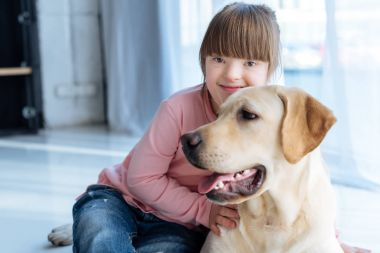 Kid with down syndrome and Labrador retriever resting on the floor