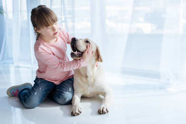 Kid with down syndrome playing with Labrador retriever