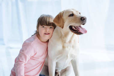 Kid girl with down syndrome embracing Labrador retriever on light background