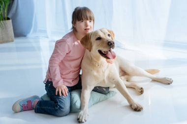 Child with down syndrome near Labrador dog on the floor