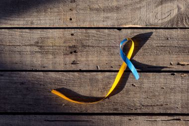 Blue and yellow ribbon as symbol of Down Syndrome Day on wooden background stock vector