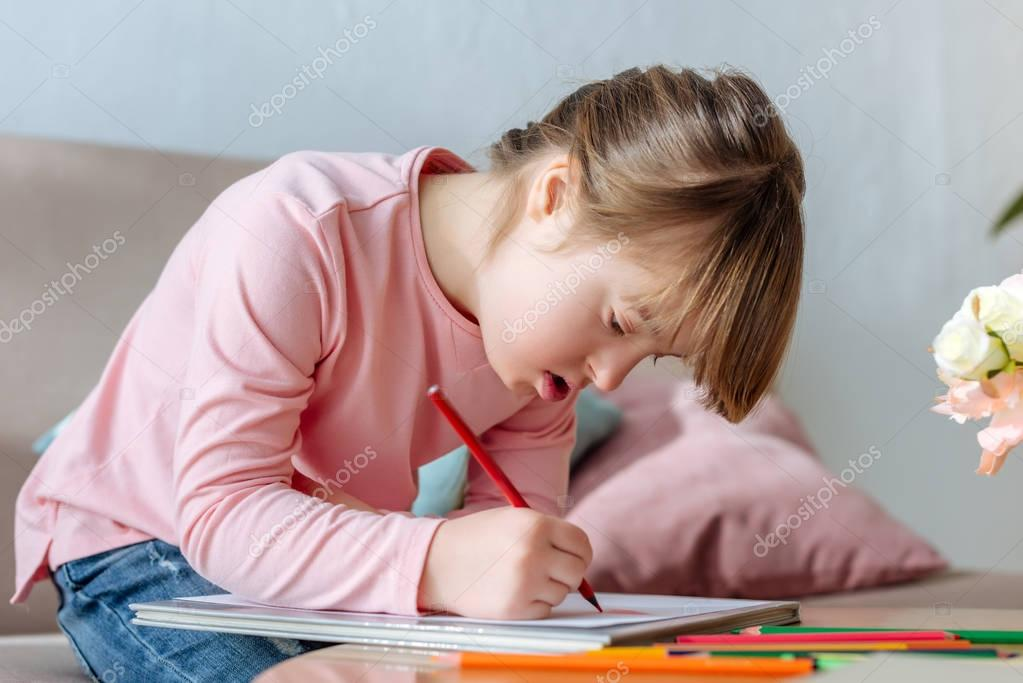 Child with down syndrome enthusiastically drawing with colorful pencils