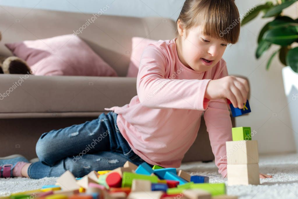 Child with down syndrome playing with toy cubes on floor in cozy room