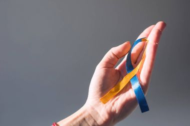 Female hand holding Down Syndrome Day symbol blue and yellow ribbon isolated on grey