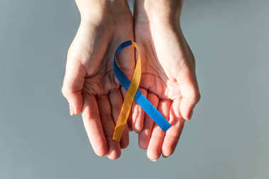 Female hands holding Down Syndrome Day symbol blue and yellow ribbon isolated on grey