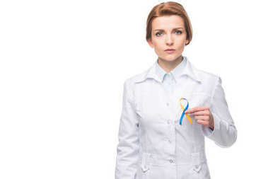 Doctor holding blue and yellow ribbon for Down Syndrome campaign isolated on white