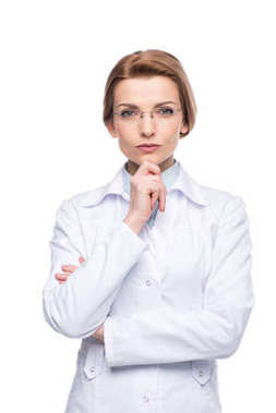 Young smiling female doctor wearing glasses with hand on chin isolated on white