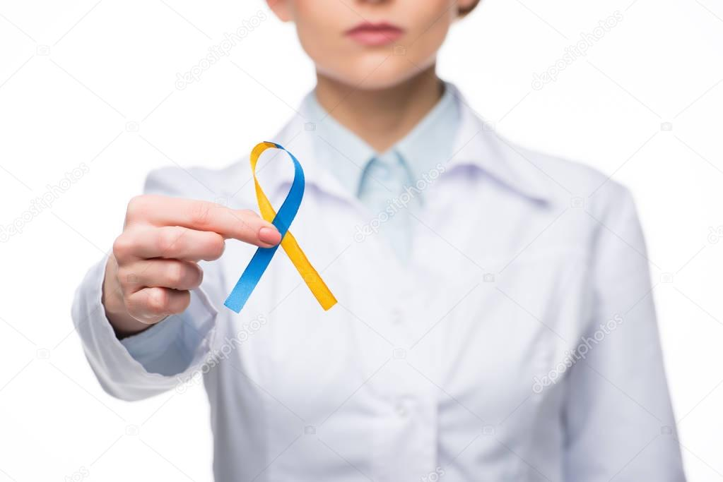 Female doctor holding blue and yellow ribbon for Down Syndrome Day isolated on white