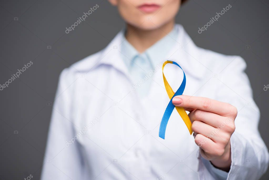 Female doctor holding blue and yellow ribbon for Down Syndrome Day isolated on grey