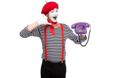 happy mime holding ultra violet retro stationary telephone and showing call me sign isolated on white