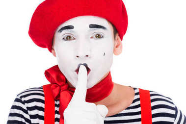portrait of mime showing silence gesture isolated on white