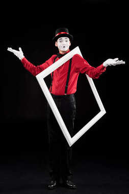 mime showing shrug gesture and holding frame on shoulder isolated on black