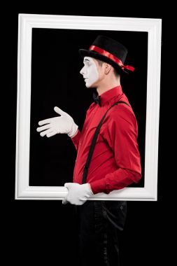 side view of mime showing hand in frame isolated on black