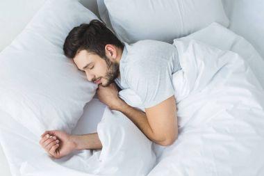 top view of bearded man sleeping on bed in bedroom