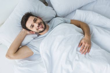 top view of cheerful man lying on bed in the morning