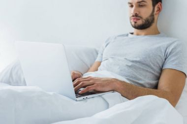 bearded man lying on bed and using laptop