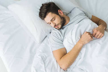 top view of bearded man sleeping on bed