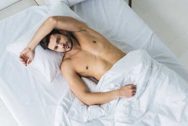 Top view of handsome shirtless sexy man lying on white bed stock vector