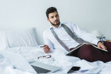 businessman lying on bed with documents and digital devices
