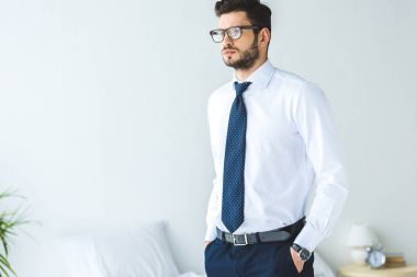 handsome businessman in white shirt and tie standing in bedroom