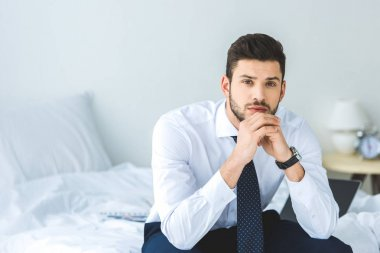 handsome businessman in white shirt and tie sitting on bed