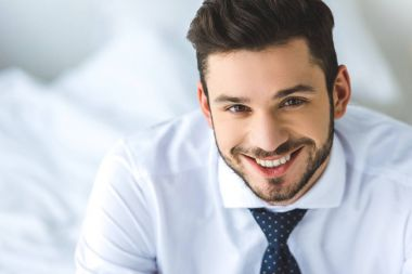 portrait of handsome businessman in white shirt and tie smiling at camera