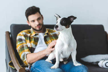 handsome man in checkered shirt sitting on sofa with dog