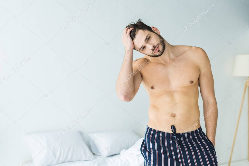 handsome shirtless man posing in bedroom in the morning