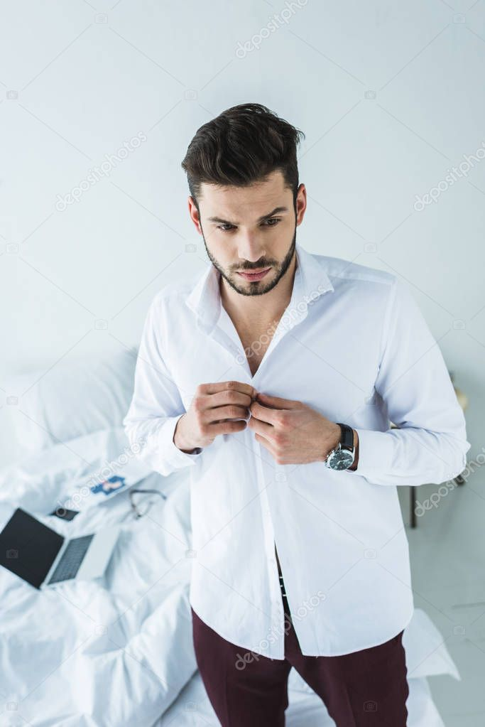 businessman wearing white shirt in bedroom