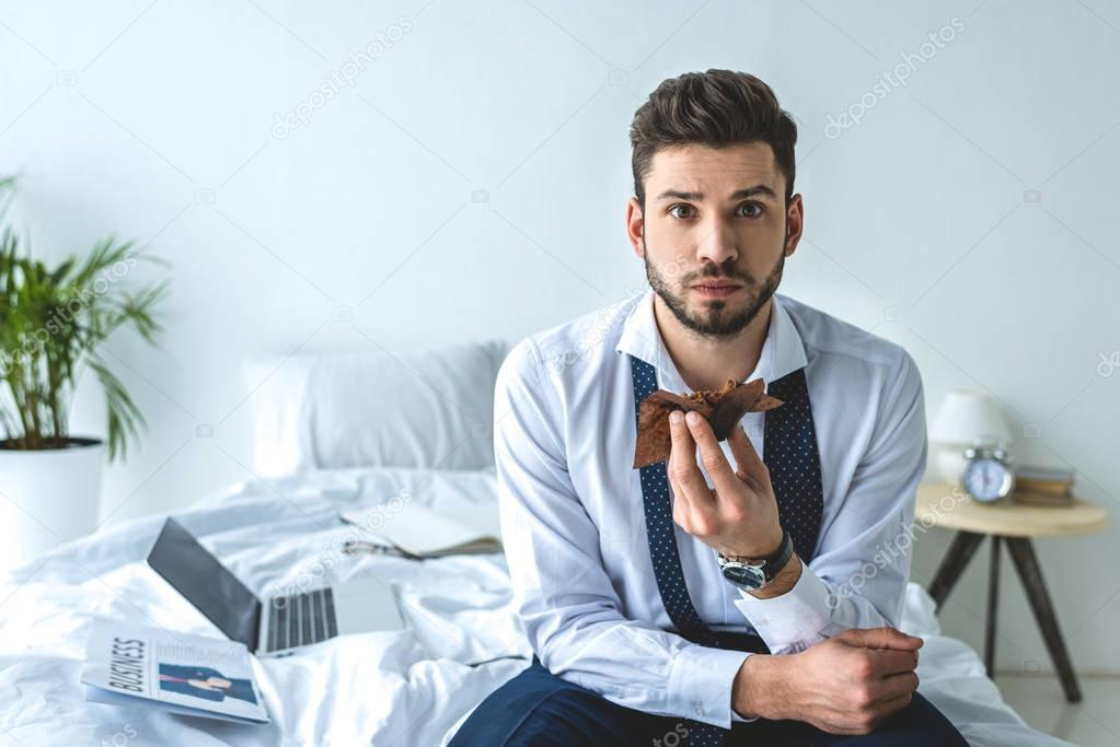 businessman eating muffin on bed with laptop and newspaper