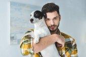 Fotografie handsome man holding jack russell terrier dog