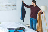 Fotografie smiling man packing clothes into travel bag in bedroom