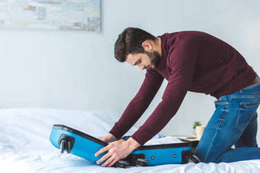 handsome man packing baggage on bed for trip
